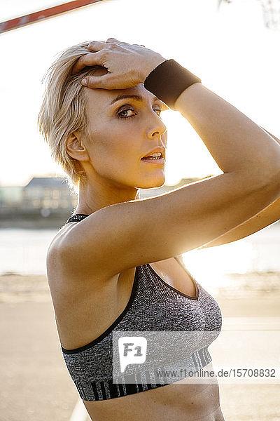Porträt einer blonden Sportlerin  Hände in den Haaren