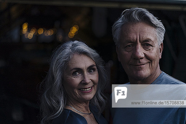 Portrait of a smiling senior couple outdoors at night