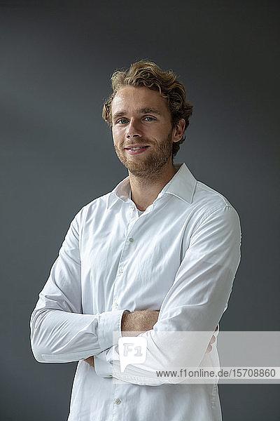 Porträt eines jungen lächelnden Geschäftsmannes mit weißem Hemd  der in die Kamera schaut