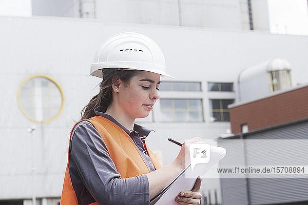Arbeitnehmerin mit Zwischenablage  die im Kraftwerk Notizen macht
