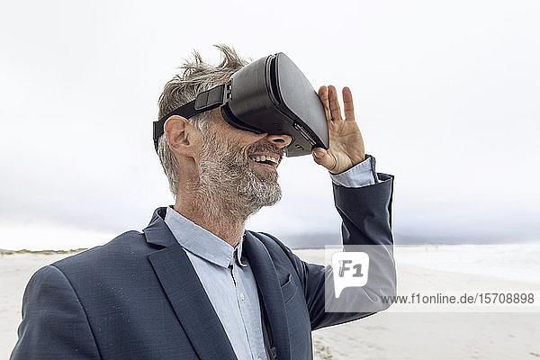 Lächelnder Geschäftsmann mit VR-Brille am Strand  Nordhoek  Western Cape  Südafrika
