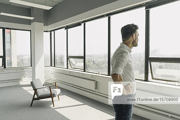 Mature businessman looking out of window in empty office