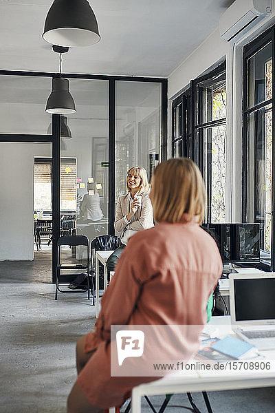 Two businesswomen having a coffee break in office
