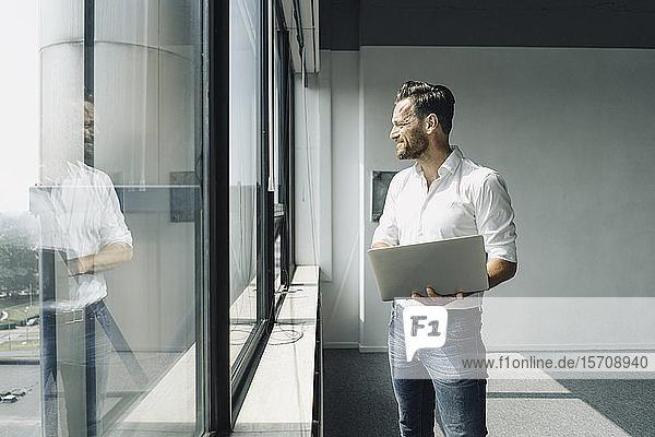 Reifer Geschäftsmann mit Laptop am Fenster im leeren Büro