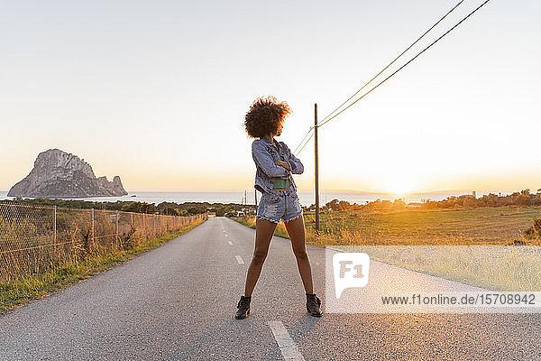 Junge Frau steht auf der Straße und betrachtet den Sonnenuntergang  Ibiza