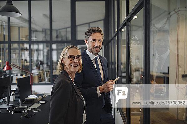 Lächelnder Geschäftsmann und Geschäftsfrau stehen beim Zeichnen auf einer Glasscheibe im Büro