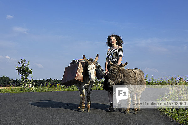 Young woman standing on country road with donkeys carrying baggage