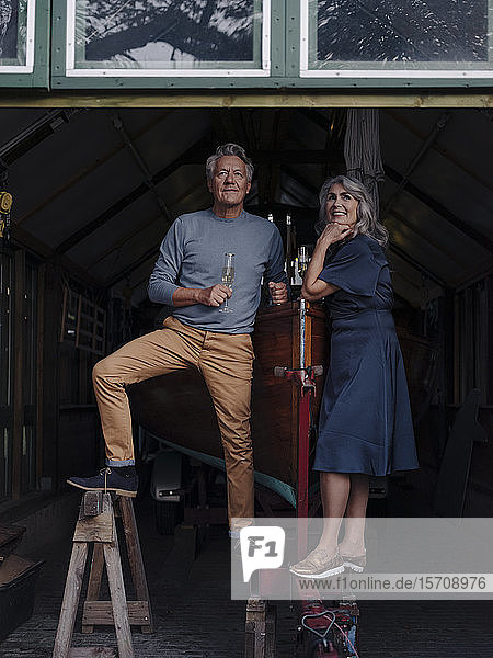 Senior couple in a boathouse with glass of champagne