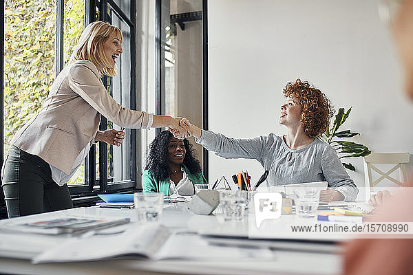Happy businesswomen having a meeting and shaking hands in office