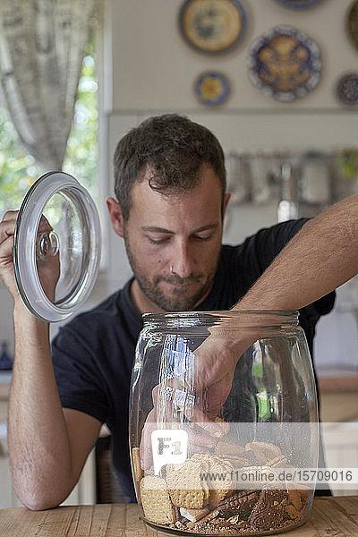 Mann sitzt in der Küche  schaut in die Keksdose  nimmt Kokkie