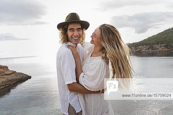 Porträt eines jungen verliebten Paares vor dem Meer stehend  Ibiza  Balearen  Spanien