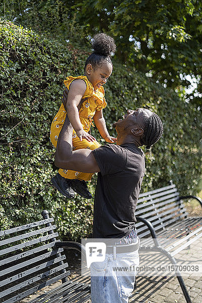 Father lifting up daughter at a bench in a park
