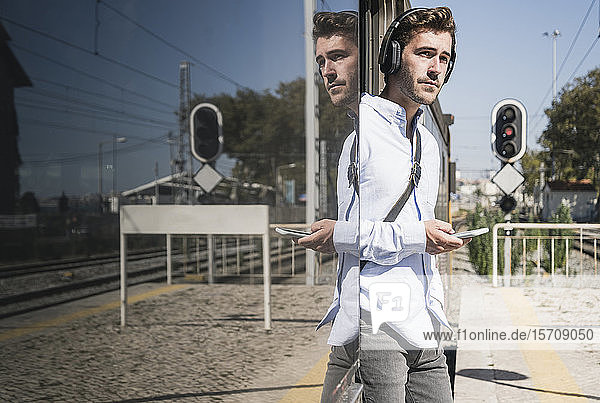 Young man with headphones and smartphone standing in train door