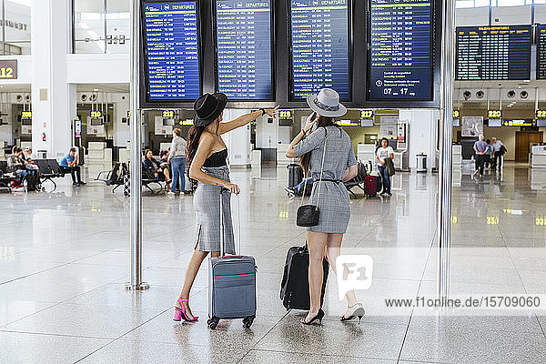 Two fashionable young women at the airport terminal checking the arrival departure board