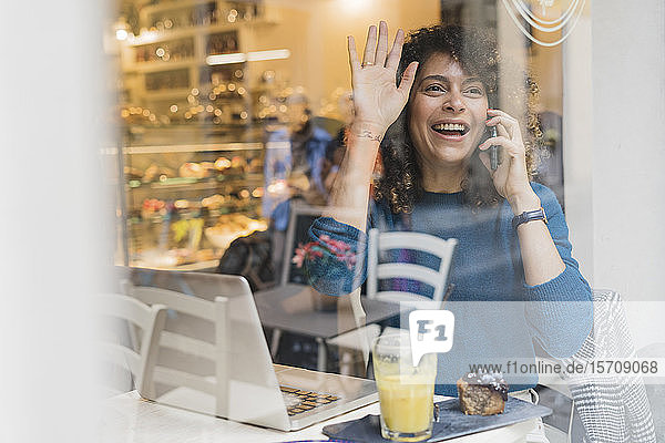 Happy woman on the phone in a cafe waving