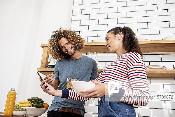Junge Frau zeigt dem Mann zu Hause in der Küche ein Smartphone