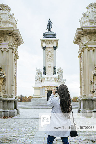 Woman taking a photo of Alfonso XII monument in El Retiro park  Madrid  Spain