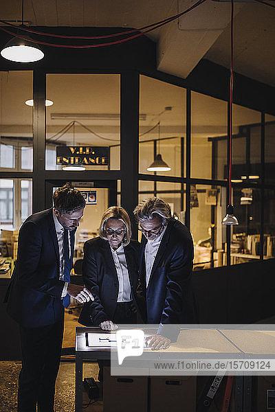 Geschäftsleute mit leuchtender Tafel sprechen im Büro
