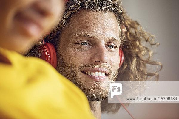 Porträt eines lächelnden  musikhörenden jungen Mannes mit Frau im Vordergrund