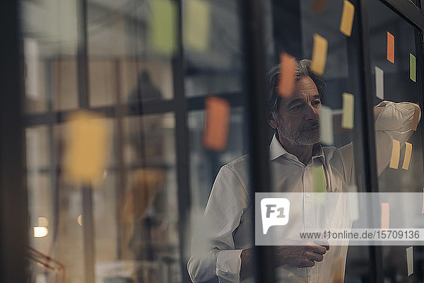 Senior businessman looking at adhesive notes at glass pane in office