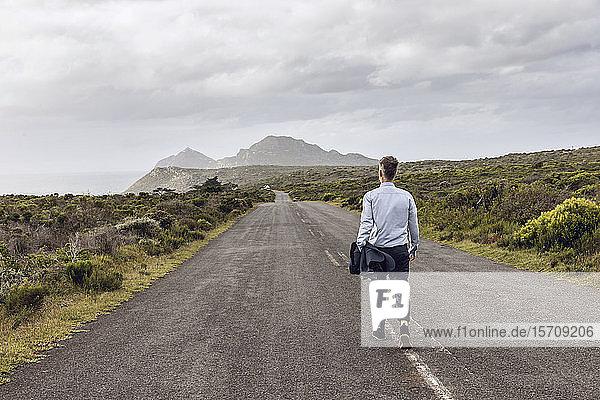 Rückansicht eines Geschäftsmannes auf einer Landstraße  Cape Point  Western Cape  Südafrika