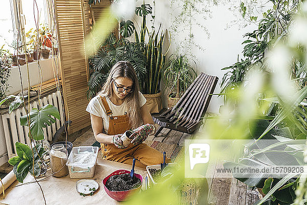 Young woman working with soil in a small gardening shop