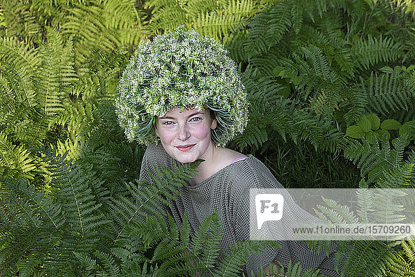 Portrait of young woman among fern wearing headpiece of flowers