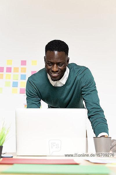 Lächelnder Mann arbeitet am Laptop am Schreibtisch im Büro