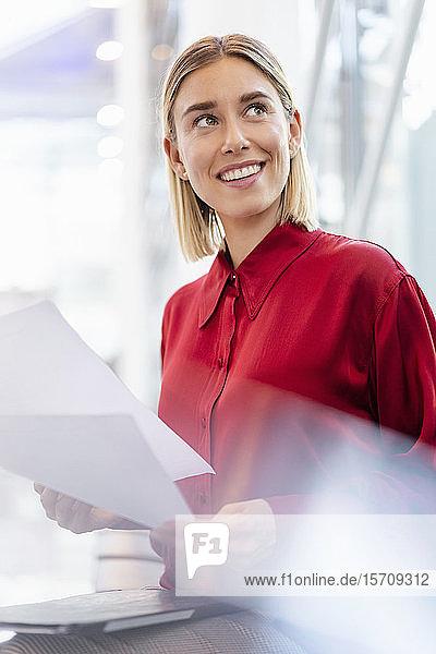 Lächelnde junge Geschäftsfrau mit Papieren sitzt im Wartebereich