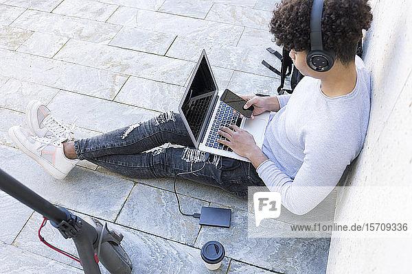 Junger Mann mit E-Scooter mit Laptop und Smartphone in der Stadt