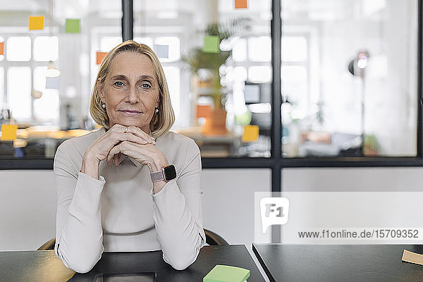 Portrait of confident mature businesswoman sitting at desk in office
