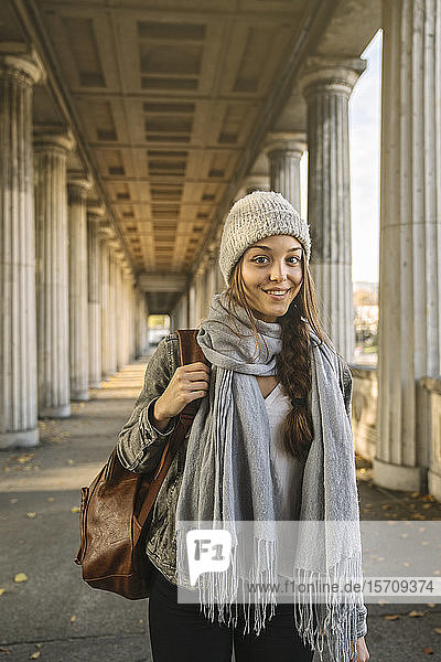 Portrait of smiling young woman in arcade in the city  Berlin  Germany