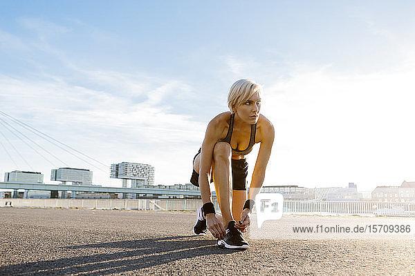 Blonde Frau beim Joggen  Schuhe binden