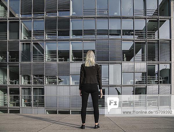 Rückansicht einer Geschäftsfrau vor einem modernen Büro