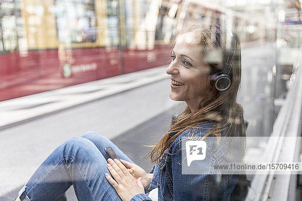 Glückliche Frau mit Smartphone und Kopfhörern wartet am Bahnhof  Berlin  Deutschland