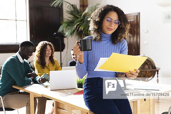 Frau mit Papier und Kaffeetasse im Büro mit Kollegen im Hintergrund