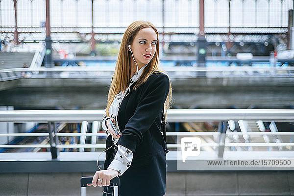 Junge Frau mit Kopfhörern und Handy dreht sich am Bahnhof um