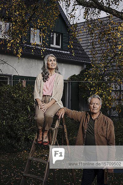 Älteres Ehepaar mit einer Leiter im Garten seines Hauses