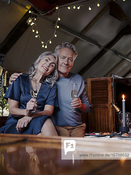 Portrait of senior couple having a candlelight dinner on a boat in boathouse