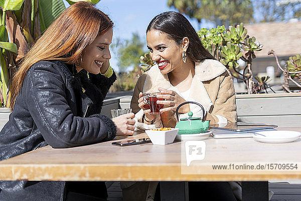 Zwei Freundinnen trinken Tee im Freien in einem Café