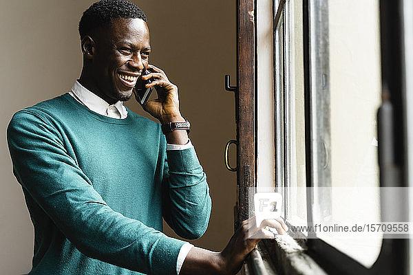 Glücklicher Mann telefoniert am Fenster