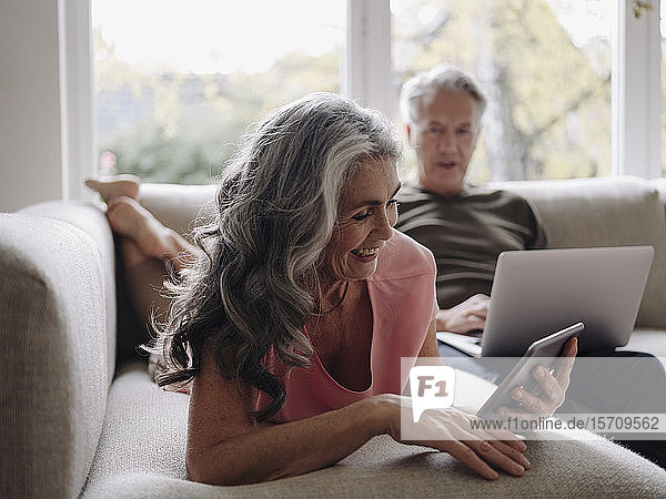 Senior couple relaxing on couch at home using tablet and laptop