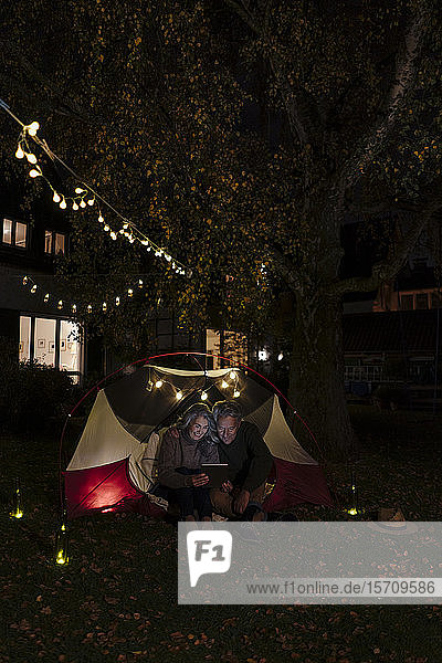 Senior couple with tablet camping in garden of their home at night