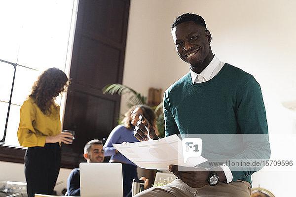 Porträt eines lächelnden Mannes im Büro mit Kollegen im Hintergrund