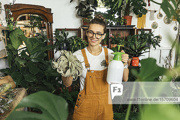 Smiling young woman caring for plants in a small shop