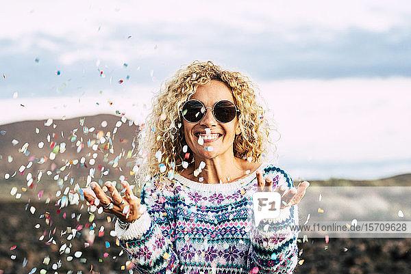 Porträt einer glücklichen blonden Frau  die mit Konfetti feiert  Teneriffa  Spanien