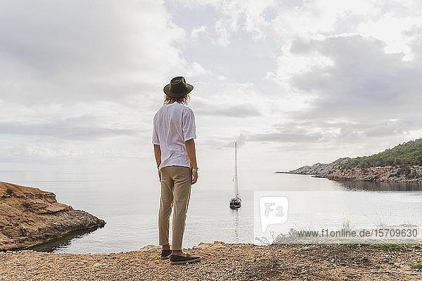 Rückansicht eines jungen Mannes  der vor dem Meer steht und auf das Meer blickt  Ibiza  Balearen  Spanien