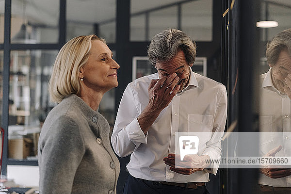 Happy businessman and businesswoman working on sticky notes at glass pane in office