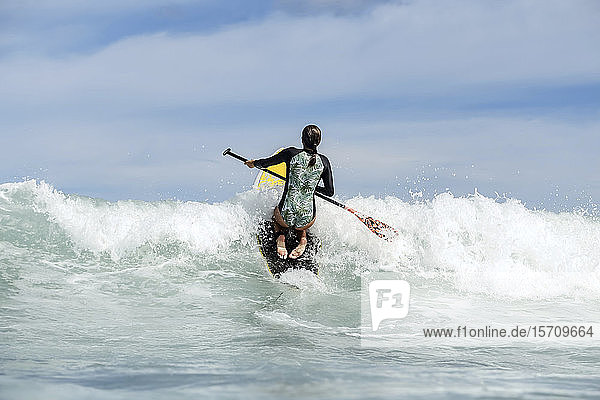 Rear view of female SUP surfer  Bali  Indonesia
