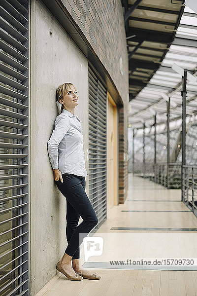 Junge Geschäftsfrau lehnt an einer Wand in einem modernen Bürogebäude